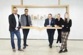 Verstas Architects, KOKO3 and the mayor of Helsinki pose in the lobby of the Helsinki City Hall
