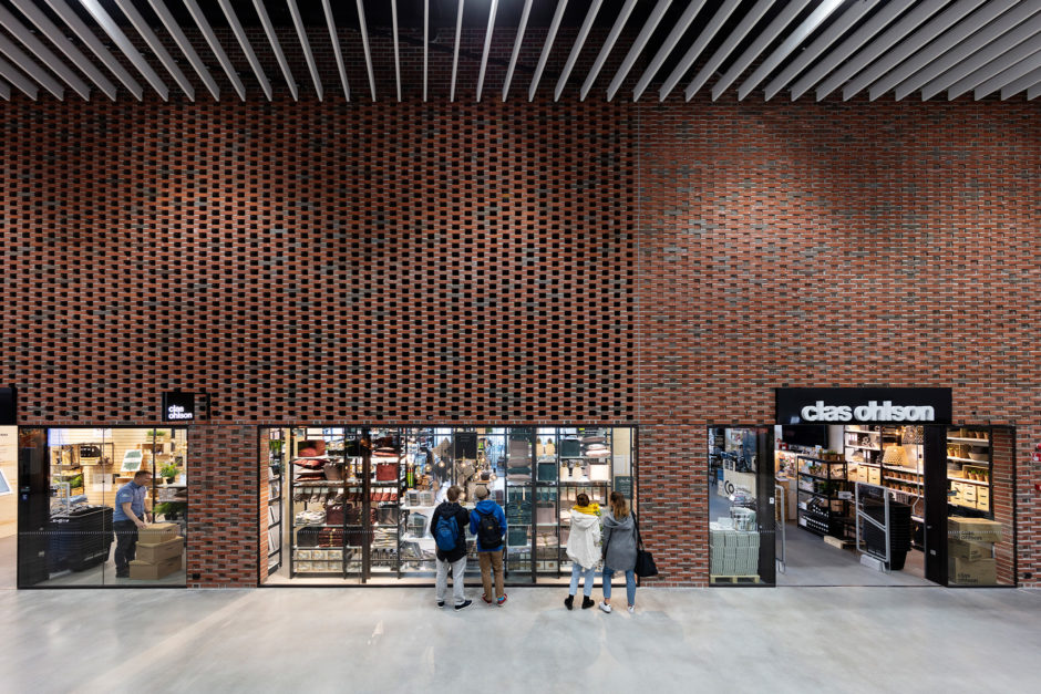 Retail spaces and brick interiors in the Aalto University campus building designed by Verstas Architects